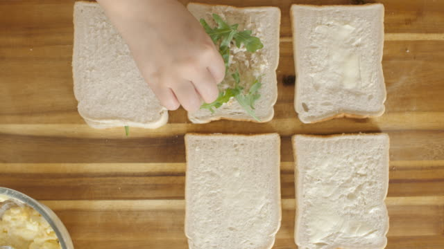 hand making chicken mayo sandwich with rocket leaves - sandwich stock videos & royalty-free footage