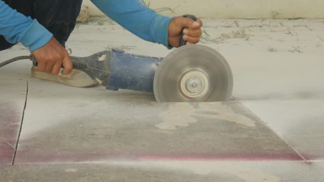 Hand man snijden betonvloer met machine.