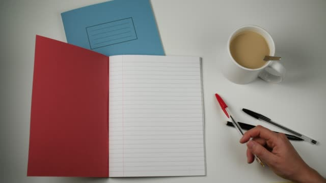 stockvideo's en b-roll-footage met hand moving pen next to open red notebook with copy space - table top shot