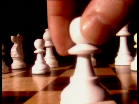 Hand moving sequence of chess pieces; white pawn black pawn white knight black knight