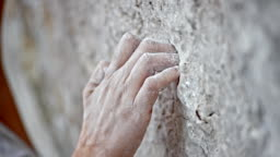 PAN Hand of a climber gripping the rocky wall