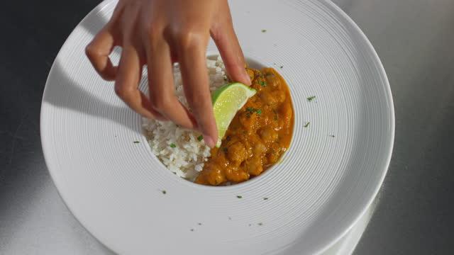 ビーガンひよこ豆カレーにライムスライスを追加する女性シェフのslo mo ldハンド - カレー料理点の映像素材/bロール