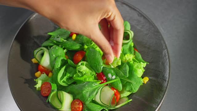 vídeos de stock, filmes e b-roll de slo mo ld mão de uma chef fêmea adicionando sal a uma salada - prato