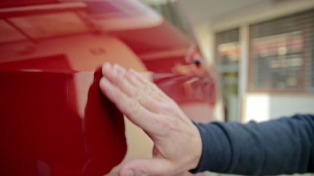 hand of a man checking the scratches on his red car - lucidare video stock e b–roll