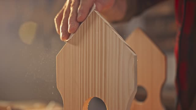 vídeos de stock e filmes b-roll de slo mo hand of a man finishing the surface of a bird house using sandpaper - artesão