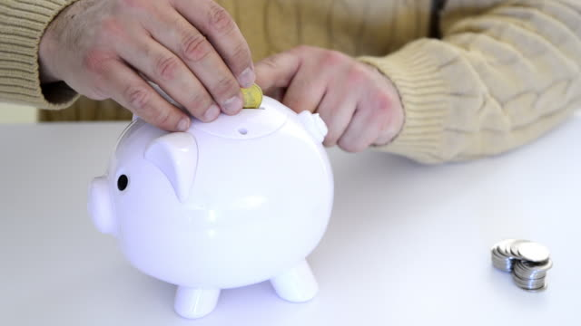 hand of a man putting money coins in piggy bank - traditionally canadian stock videos & royalty-free footage