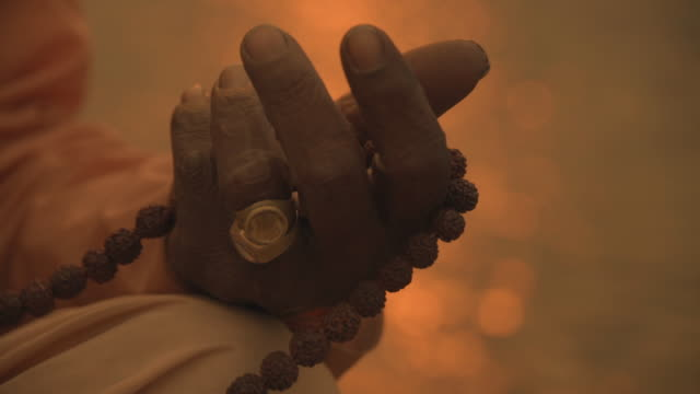 c/u hand of a sadhu w/ prayer beads in the ganges river - prayer beads stock videos & royalty-free footage
