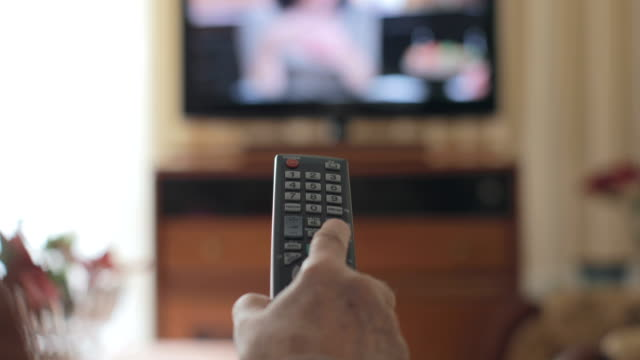 Hand of a senior man holding a tv remote control