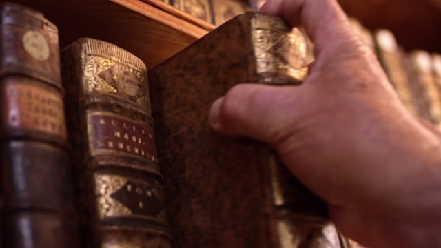 ds hand of a senior man taking an old book from the shelf - bookshelf stock videos & royalty-free footage