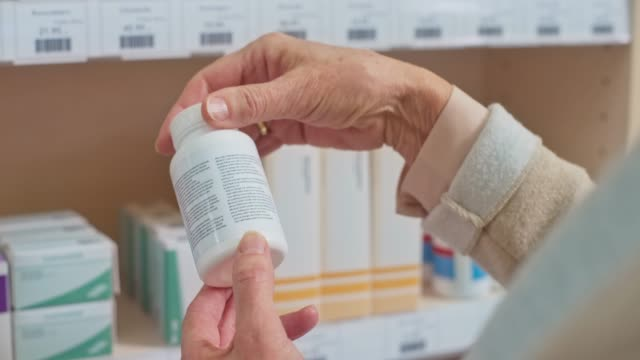 hand of a senior woman taking a medicine bottle off the shelf at the chemist's - pill bottle stock videos & royalty-free footage