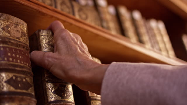 ds hand of a senior woman taking an old book from the shelf - literature stock videos & royalty-free footage