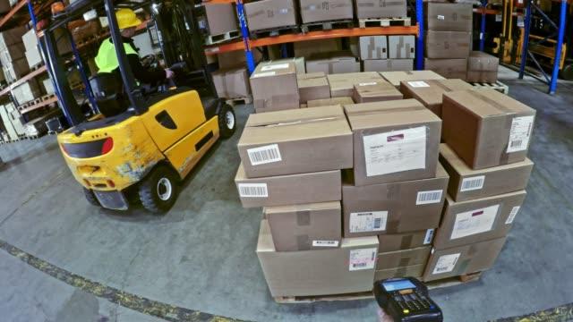 スキャナーを押し、パレットの上にパッケージをスキャン倉庫作業員のpov手 - 倉庫作業員点の映像素材/bロール