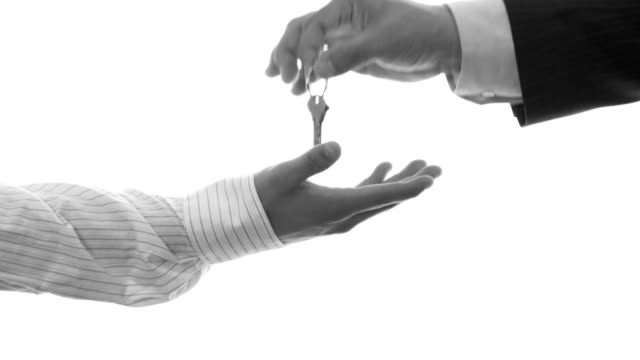 hand of an older man passing a key to a younger male - key stock videos & royalty-free footage