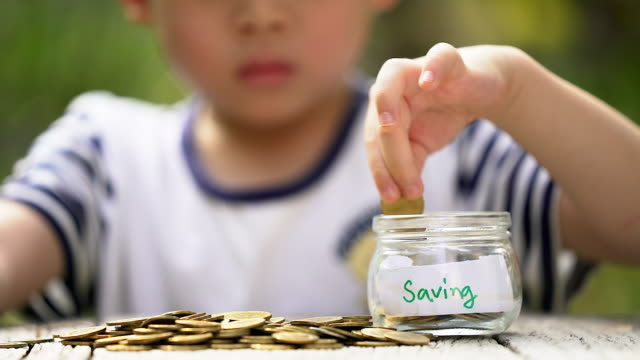 Hand of asian boy with golden coins saving golden ,saving concept, saving money ,business concept.