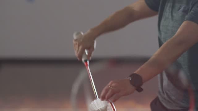 vidéos et rushes de main des joueurs chinois asiatiques de badminton jouant dans le terrain de badminton - badminton sport