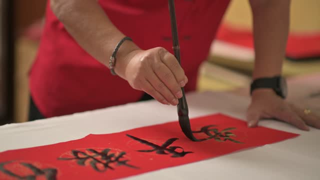 hand of asian chinese male practising chinese caligraphy for coming chinese new year celebration home decoration purpose with prosperity and good wording by writing it on a red piece of paper - skill stock videos & royalty-free footage