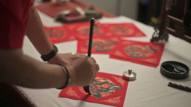 hand of asian chinese male practising chinese caligraphy for coming chinese new year celebration home decoration purpose with prosperity and good wording by writing it on a red piece of paper - celebratory event stock videos & royalty-free footage