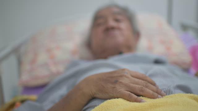 vídeos y material grabado en eventos de stock de mano de asiático chino anciano con tubo de traqueotomía acostado en la cama - demencia