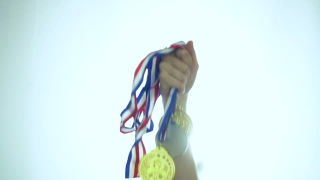 hand of athlete celebrating the win with gold medals - athleticism stock videos & royalty-free footage