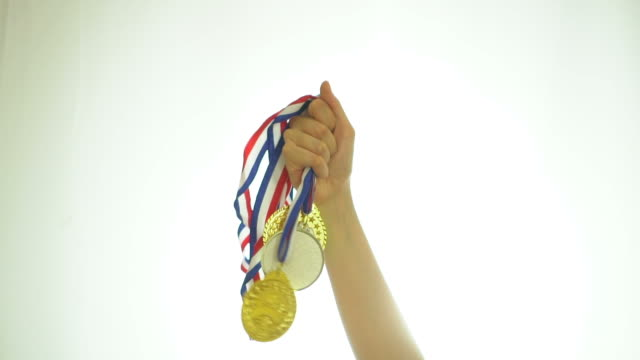 hand of athlete celebrating the win with gold medals - gold medalist stock videos & royalty-free footage