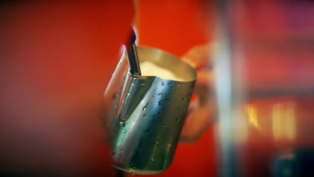 hand of barista steaming milk in the stainless steel milk pitcher at the coffee shop. - milk jug stock videos & royalty-free footage