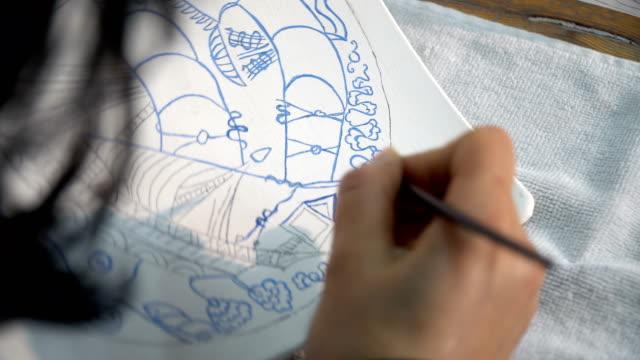 hand of ceramist artist working on decorative tiles - oggetto creato dall'uomo video stock e b–roll
