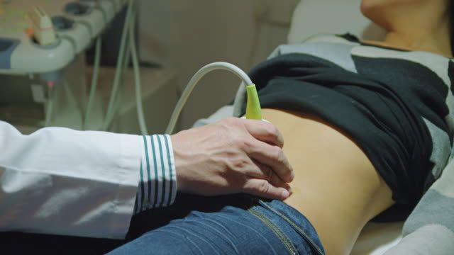 cu hand of doctor performing ultrasound examination on female patient - ultrasound stock videos and b-roll footage