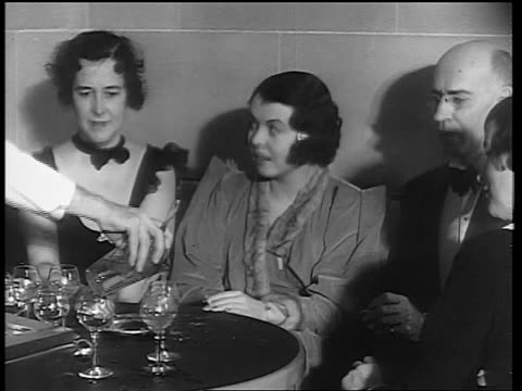 b/w 1933 hand of male bartender pouring drinks for group sitting at table / end of prohibition - anno 1933 video stock e b–roll
