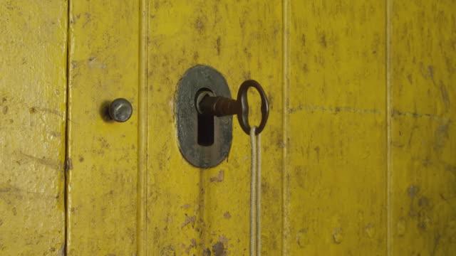ECU hand of man turns big key in closed wooden door, pushes door open to reveal an almost black room