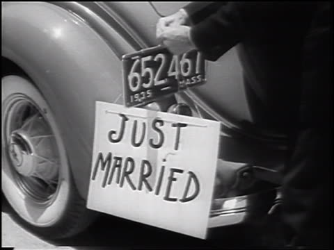 "b/w 1935 hand of man tying ""just married"" sign to license plate of car - just married stock videos and b-roll footage"
