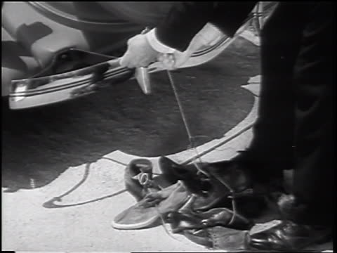 b/w 1935 hand of man tying string of shoes to bumper of car - 1935 stock videos & royalty-free footage