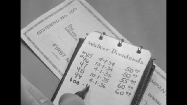 cu hand of person using pen to write payment dates and amounts of dividends hand turns over dividend certificate and writes on back of it / two close... - tighten stock videos and b-roll footage