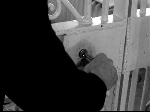 1956 cu hand of prison guard unlocking metal gate w/ key + walking through door - security screen stock videos & royalty-free footage