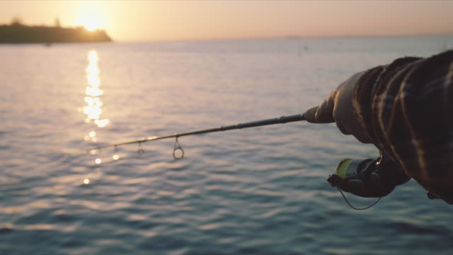 a hand of someone fishing at sunset, mornington peninsula, victoria, australia - fishing stock videos & royalty-free footage