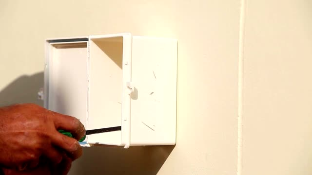 hand of technician worker using screw driver to screwing screw for install cable electric wire box, close up shot. - cable box stock videos and b-roll footage