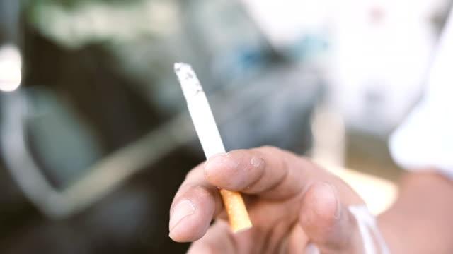 vídeos de stock, filmes e b-roll de mão do homem fumando - smoking