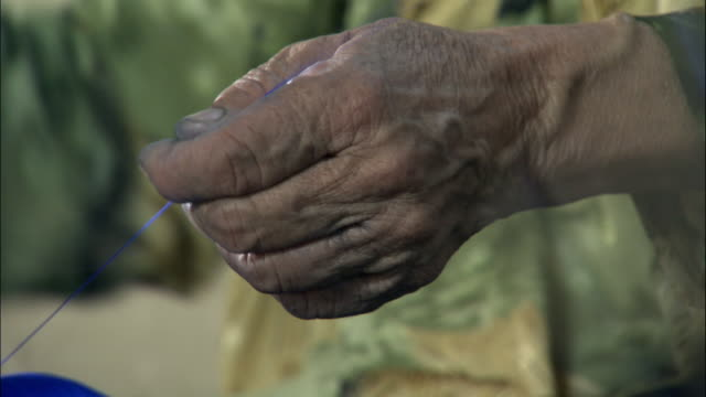 Hand of woman as she spins blue silk, Hetian, Xinjiang, China