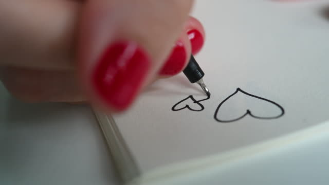 hand of woman doodling hearts in notebook - red pen stock videos & royalty-free footage