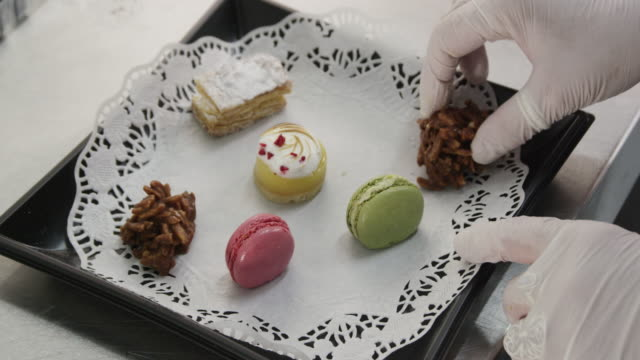 ECU hand of woman dressing catering plate with sweets, RED R3D 4K