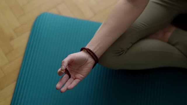vidéos et rushes de main de la femme tenant des perles mala et méditant à la maison - assis en tailleur