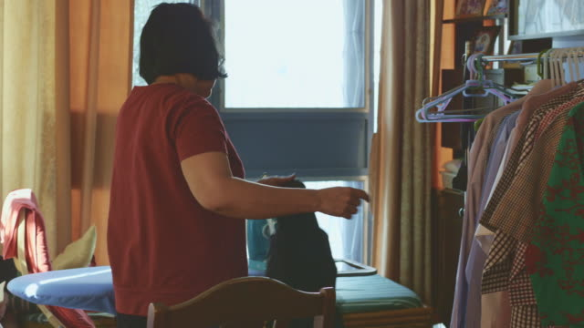 hand of woman ironing clothes on the table - lavori di casa video stock e b–roll