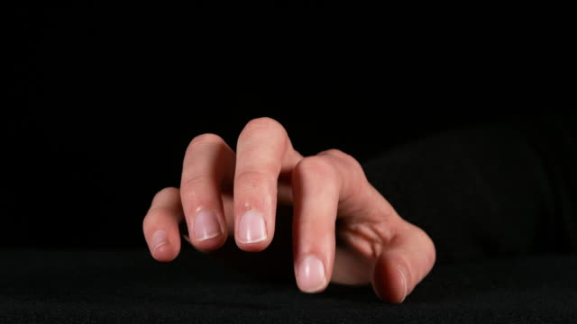 Hand of Woman making Sign against Black Background, Real Time 4k