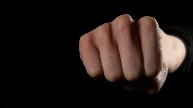 vídeos de stock, filmes e b-roll de hand of woman making sign against black background, real time 4k - posição de combate