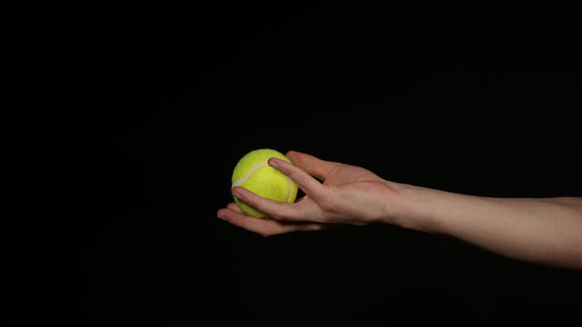 vídeos de stock e filmes b-roll de hand of woman throwing a ball of tennis against black background, slow motion 4k - bola de ténis