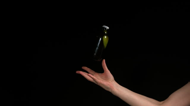 vidéos et rushes de hand of woman throwing a bottle of beer against black background, slow motion 4k - bouteille