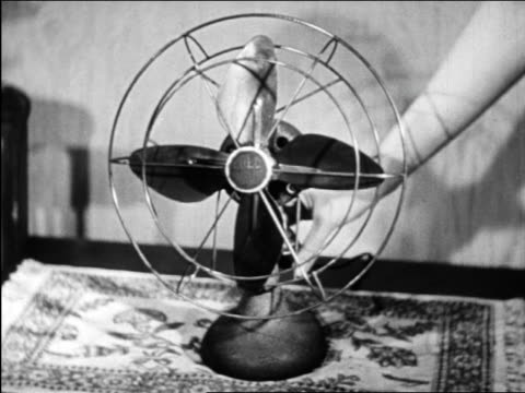 b/w 1948 hand of woman turning on electric fan / industrial - ventilator stock-videos und b-roll-filmmaterial