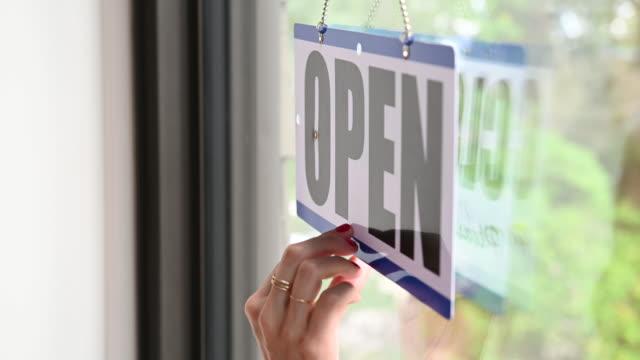 vídeos y material grabado en eventos de stock de hand of woman turning open sign - escaparate de tienda