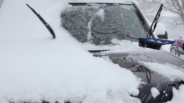 cu hand of young woman cleaning snow off car / richmond, virginia, usa - windschutzscheibe stock-videos und b-roll-filmmaterial