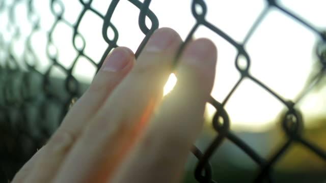 Hand auf Zaun spielt mit Sonne in Zeitlupe