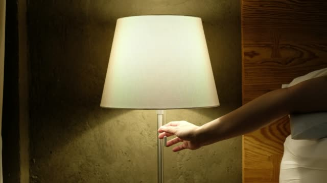 hand open and close  head lamp near bed in bedroom - lampada elettrica video stock e b–roll